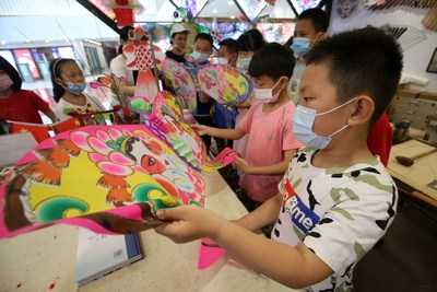 Photo taken on July 8 showed that children were learning about kite-making in the Shihuyuan community in Weifang.