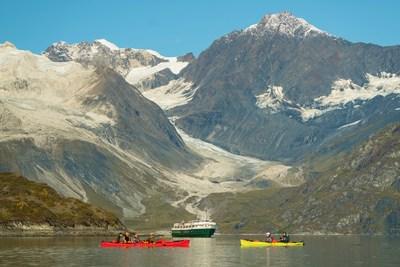 Kayaking glassy Alaskan waters in front of the Wilderness Adventurer.